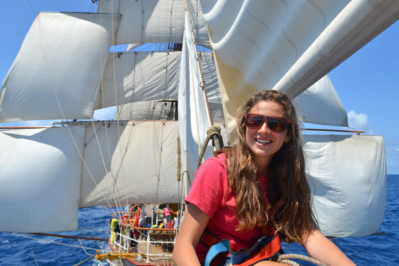 Trainee sitting on the bow of a tall ship